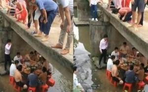 一桌人在桥下水里吃席 新人大婚为避暑流水席
